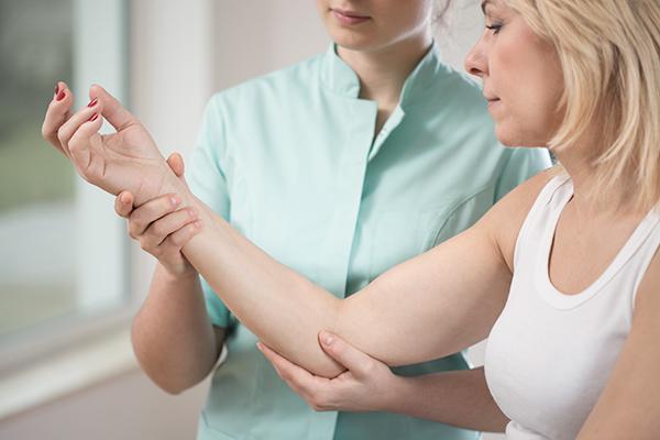 Behandler undersøker arm til pasient