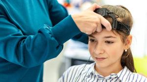 Barn sitter i stor med apparat på hodet